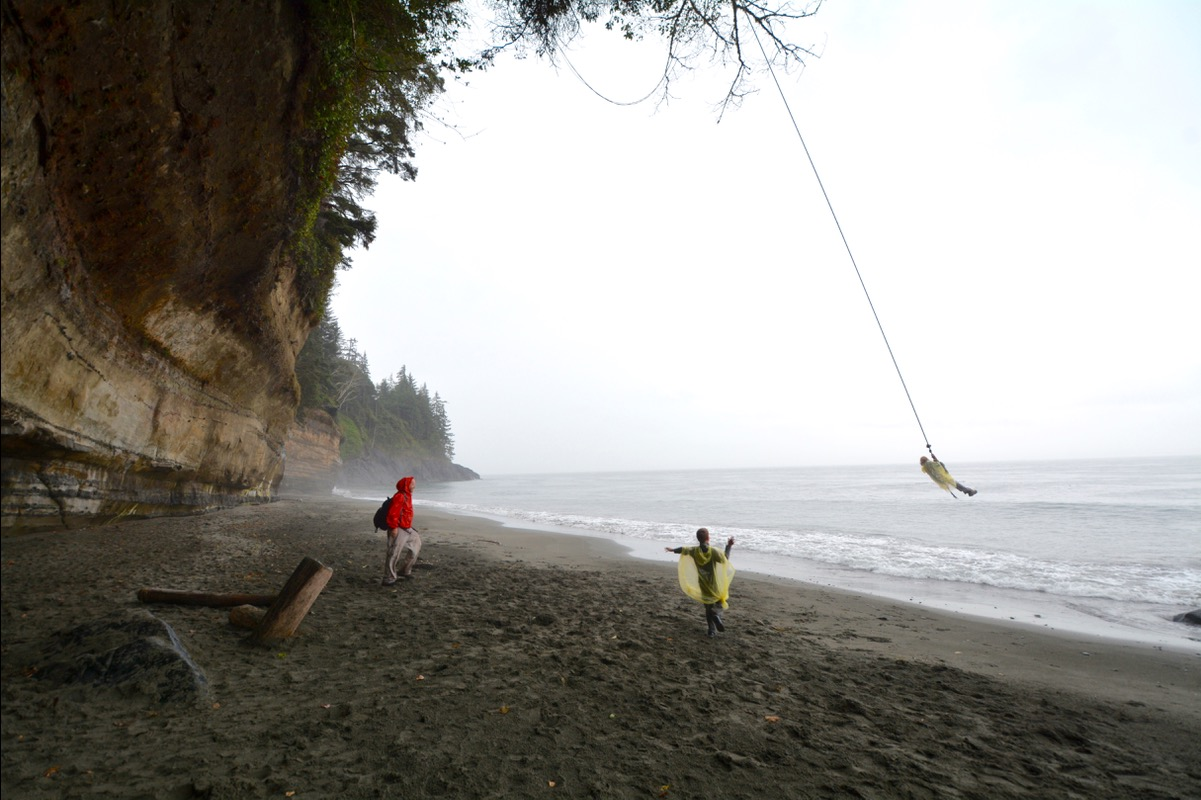 A family enjoys a rope swing on the beach along Oregon's coastline