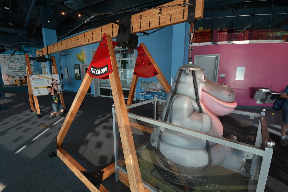 A young boy demonstrates a flucrum by lifting a huge hippo caricature in TELUS World of Science in Vancouver BC