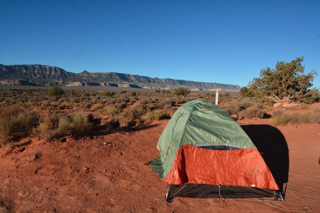 An orange and green tent on red sandstone in Grand Staircase Escalante National Monument in Utah