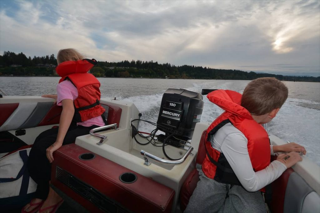 Kids looking off the back of a motorboat on Cowichan Bay, Vancouver Island BC