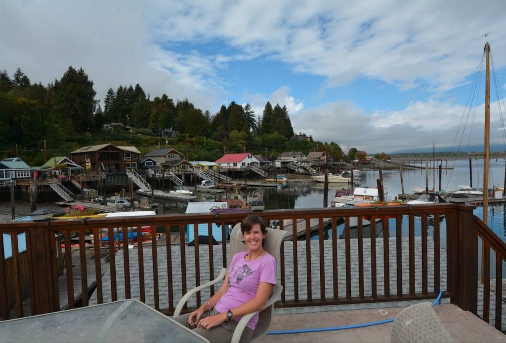 Beautiful woman sitting atop a float home in Cowichan Bay near Victoria BC