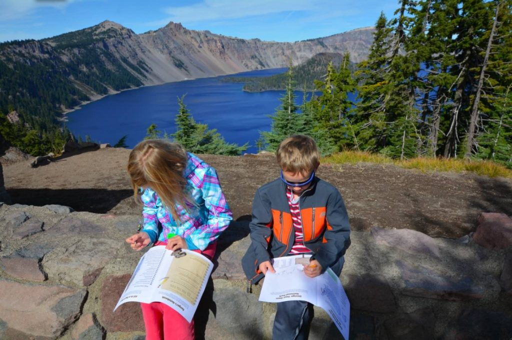 Two children working in their Junior Ranger workbooks overlooking Crater Lake inside of Crater Lake National Park