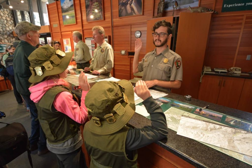 Two Junior Rangers being sworn in by a NPS Ranger