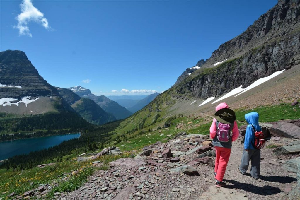 Two children hiking the Highline Trail in Glacier National Park, overlooking a lake in the valley far below