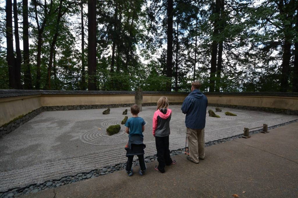 A family looks at a zen garden in a Portland public park