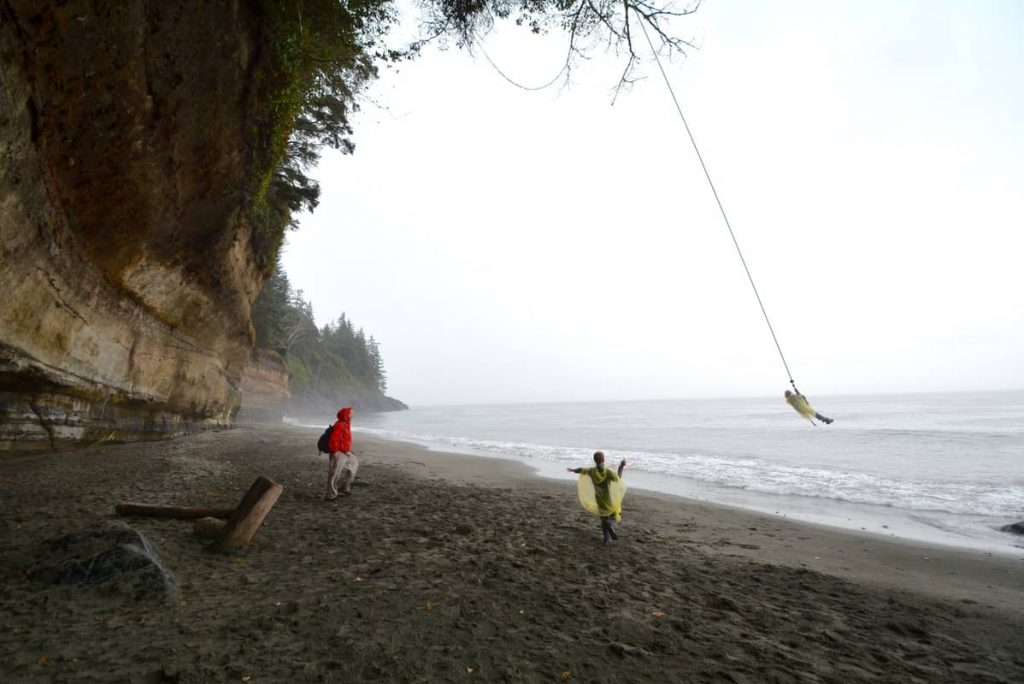 A child on a rope swing over the Pacific Ocean on the Oregon coast