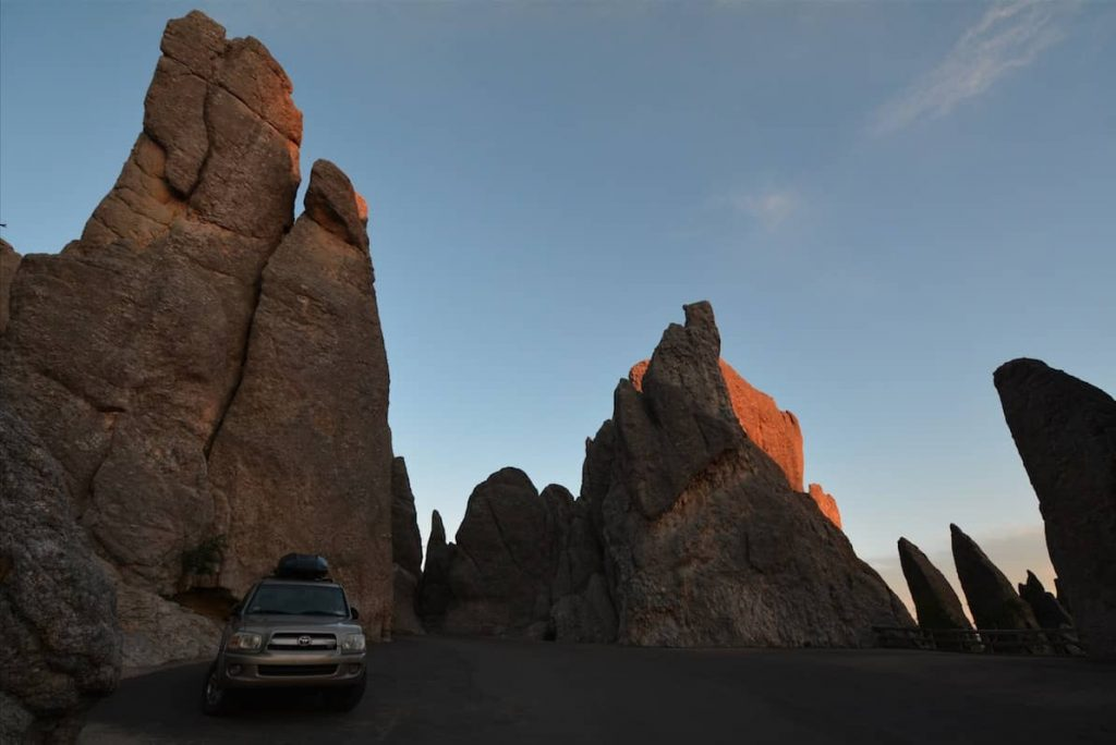 Gold Toyota Sequoia among eroded granite towers in The Needles of the Black Hills of South Dakota
