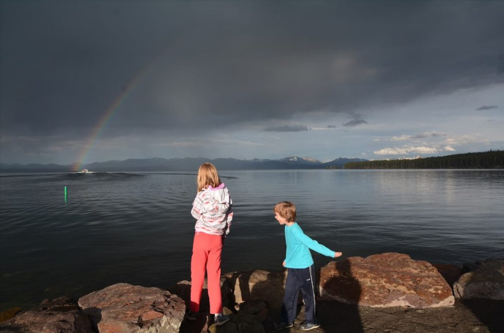 Children watch a rainbow over Yellowstone Lake in Yellowstone National Park
