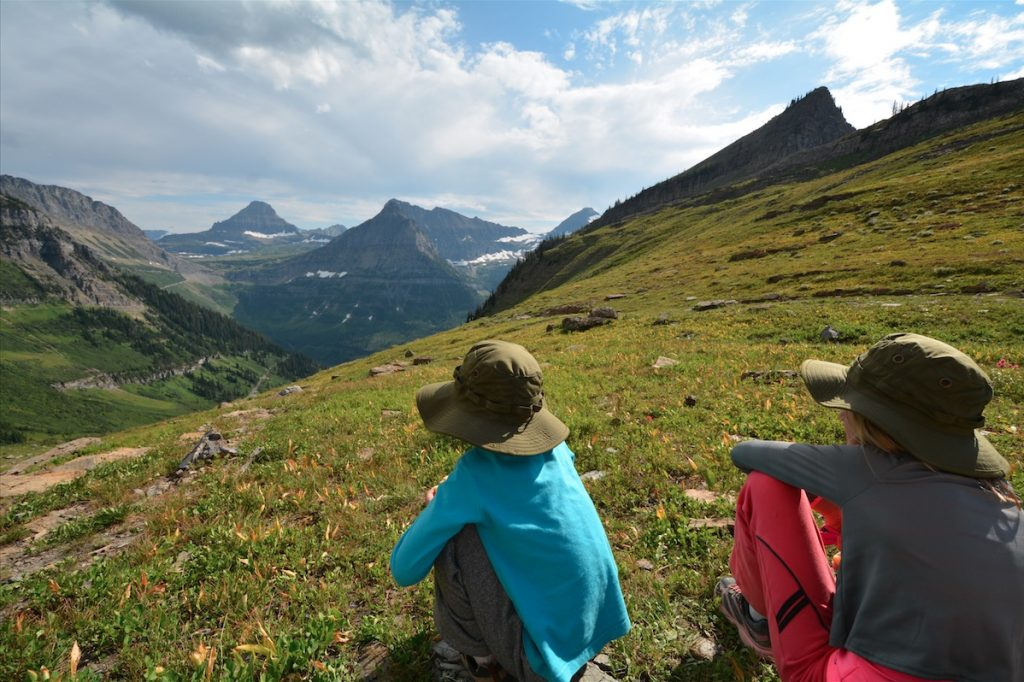 Two children in Junior Ranger hats sitting in the grass overlooking Glacier National Park
