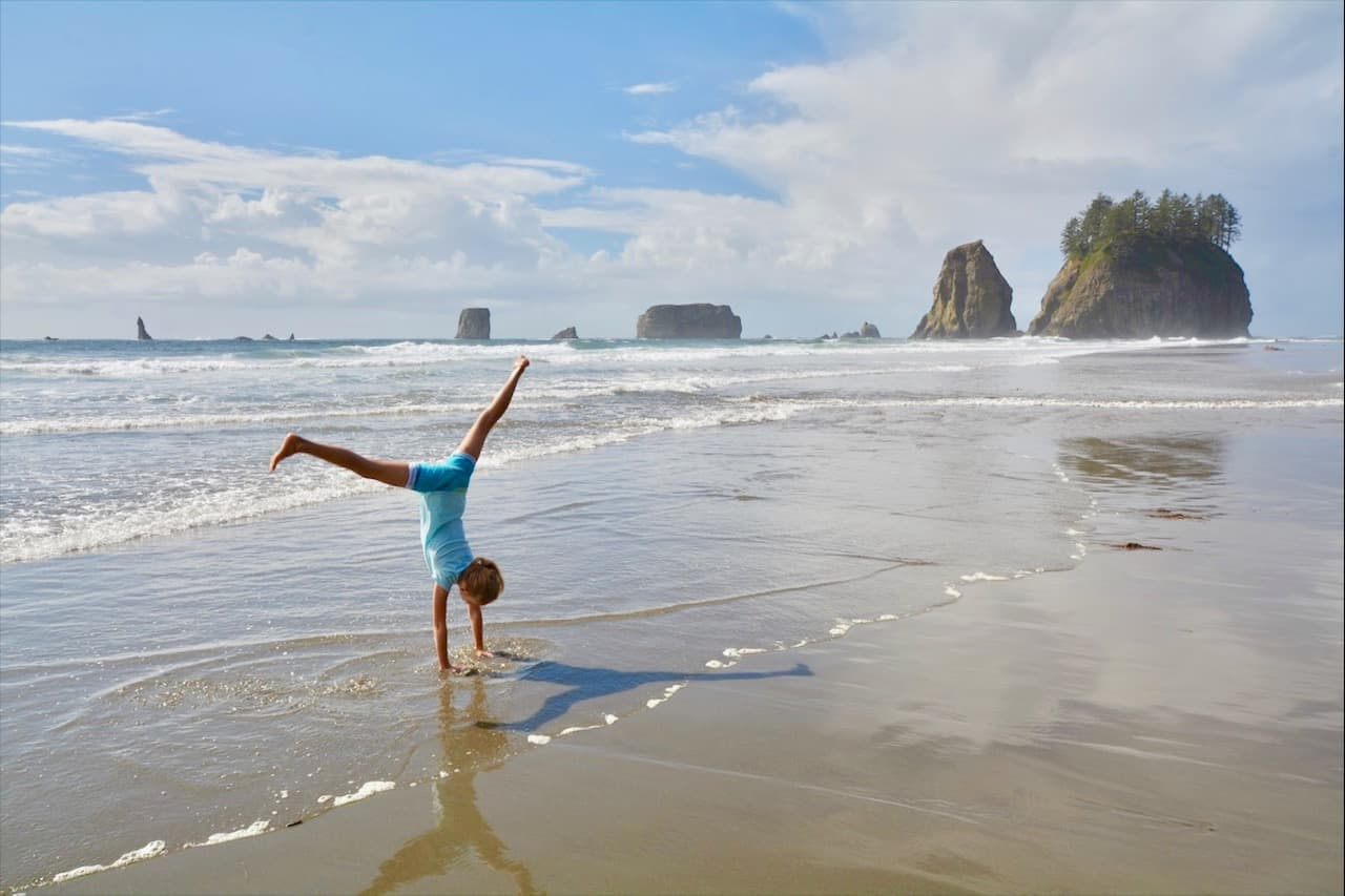 A young girl performs a cartwheel in front of sea stacks along the Oregon coastline