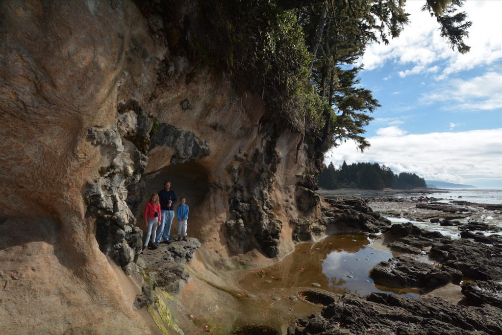 A family stands inside a shoreline cliff above tidal pools on Vancouver Island