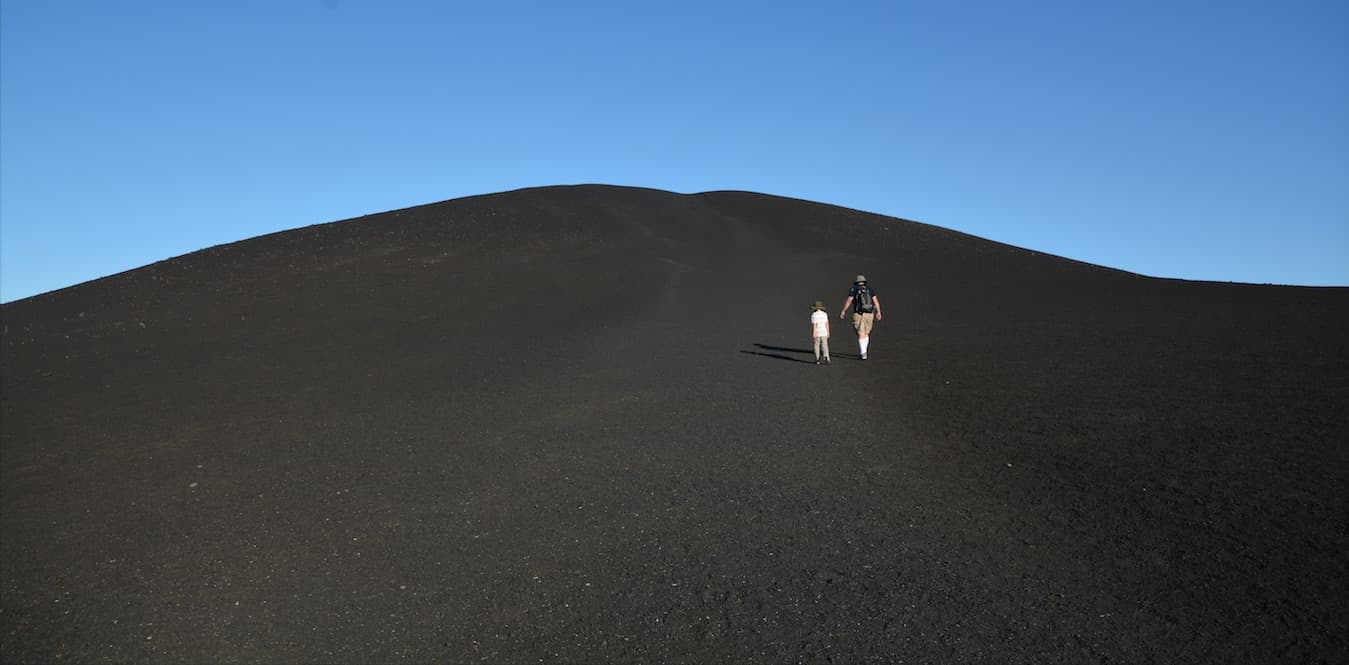 A father and son walk and talk together in Craters of the Moon National Monument in southern Idaho