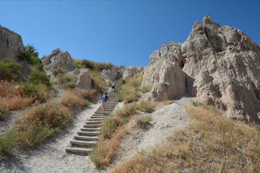 Kids climbing a huge staircase along a trail in Badlands National Park, South Dakota