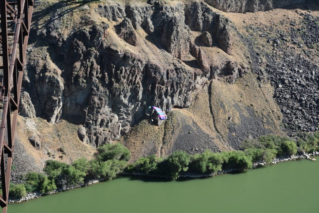 A BASE jumper's chute opens and carries him to the bottom of Snake River Canyon in Twin Falls Idaho