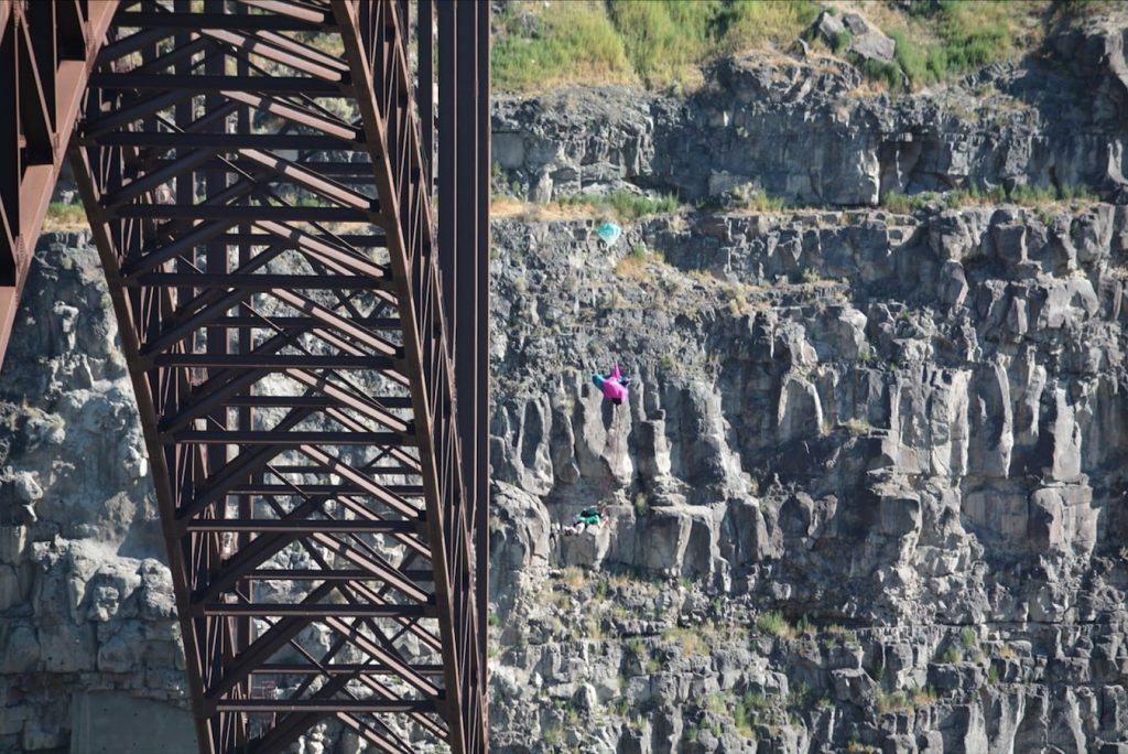 A BASE jumper's chute begins to unfurl as he plunges toward the floor of the Snake River Canyon in Twin Falls Idaho