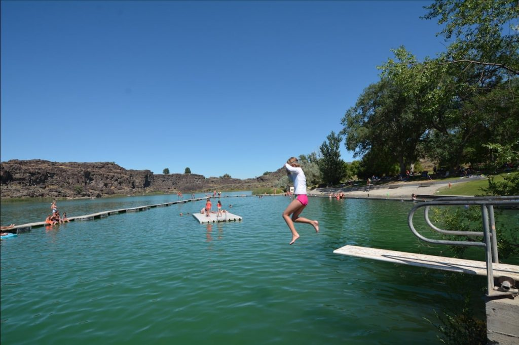 A young girl jumps from the diving board at Dierkes Lake swim beach in Shoshone State Park, near Twin Falls, Idaho