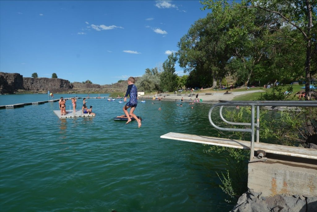 A young boy jump from the diving board at Dierkes Lake swim beach in Shoshone State Park, near Twin Falls, Idaho