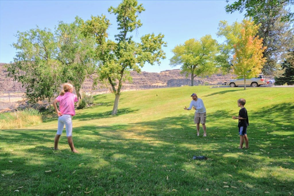 A family playing catch on the green lawns of Shoshone Falls State Park in Twin Falls, Idaho