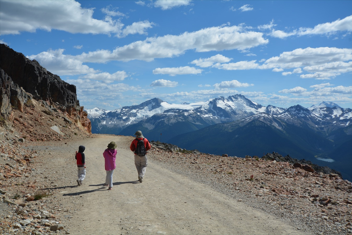 A family walks in North Cascades National Park. Glacier-topped Mount Shuksan is visible in the distance.