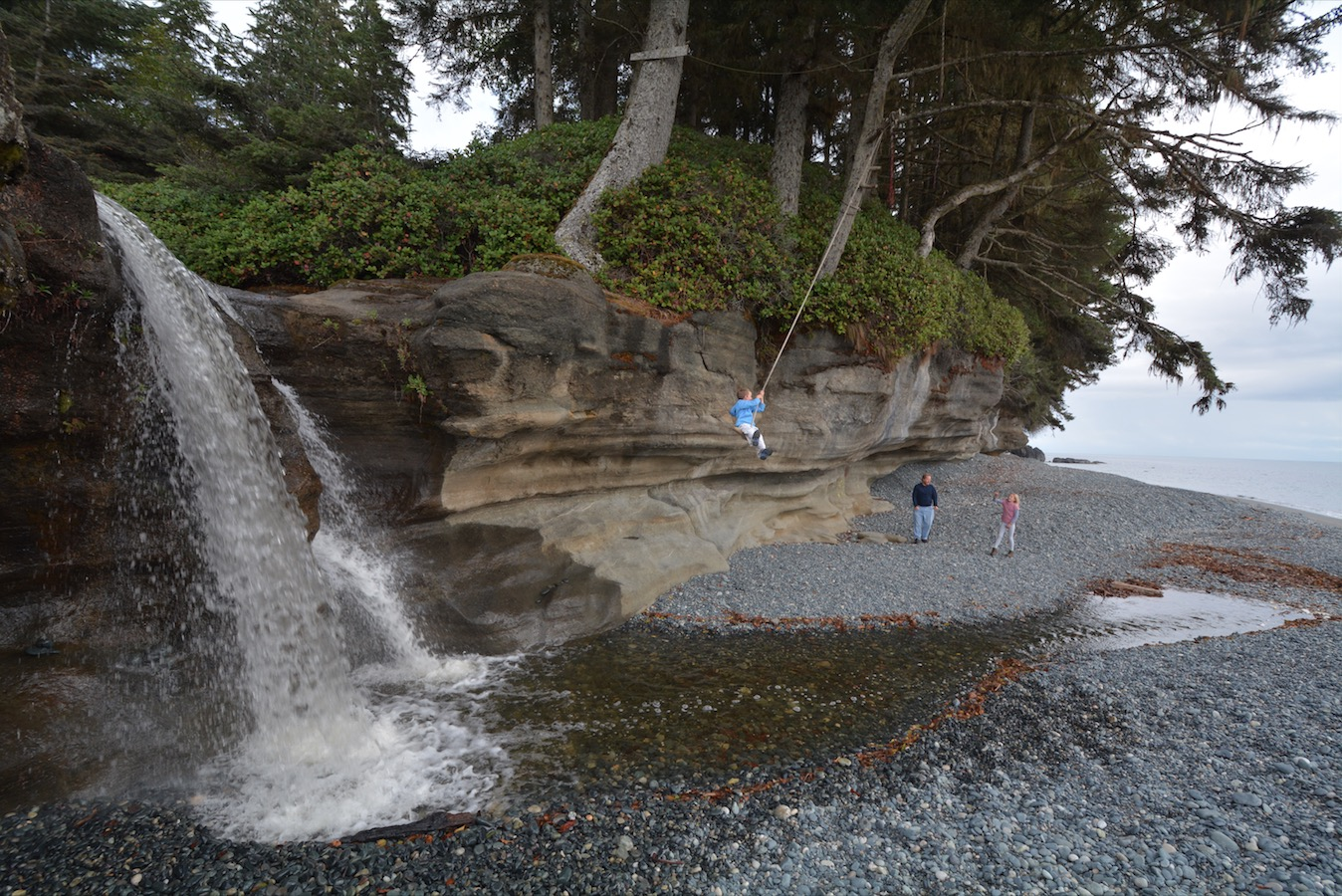 A boy swings on a rope swing near a waterfall along the Pacific coastline.