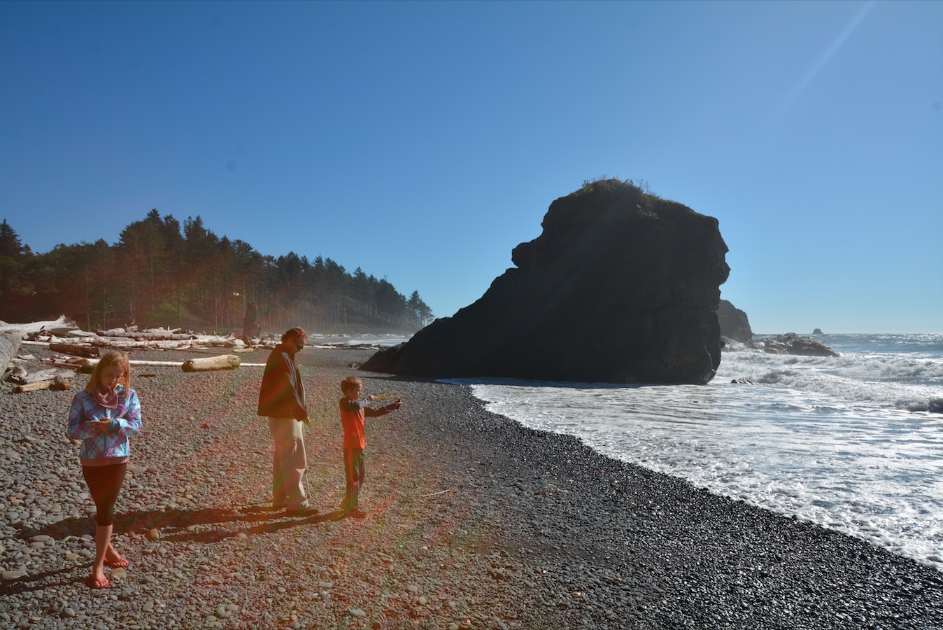 A young boy practices with his slingshot along the Pacific coast as his father looks on