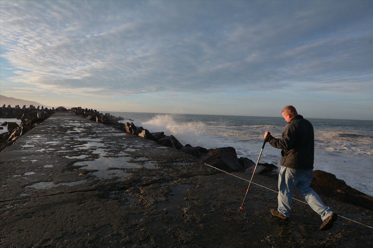 A man walks along the surge wall at Lighthouse Way in Crescent City CA