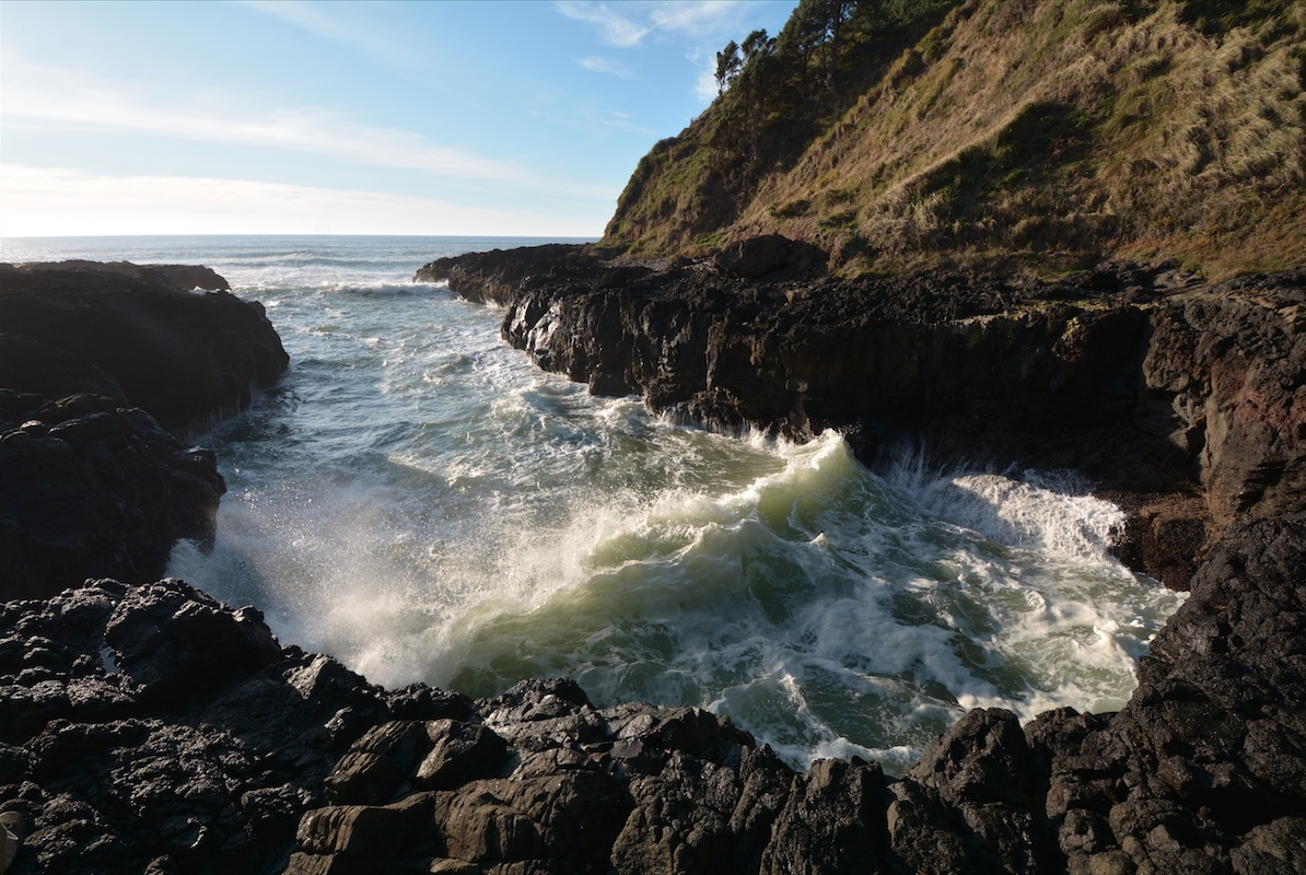 A wave rolls into a cove along the pacific coastline