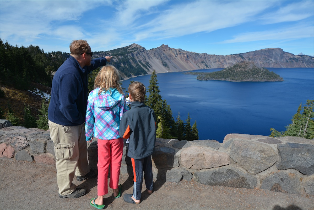 A father points out a volcanic island in the middle of crater lake to his children