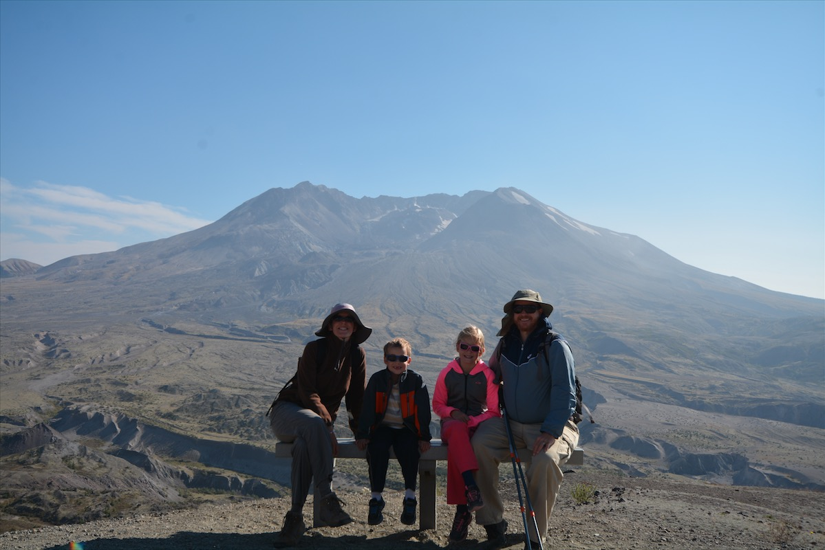 A family of four sits in front of Mount St. Helens