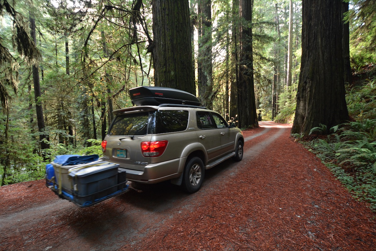 Gold 2006 Toyota Sequoia with cargo platform driving through a forest