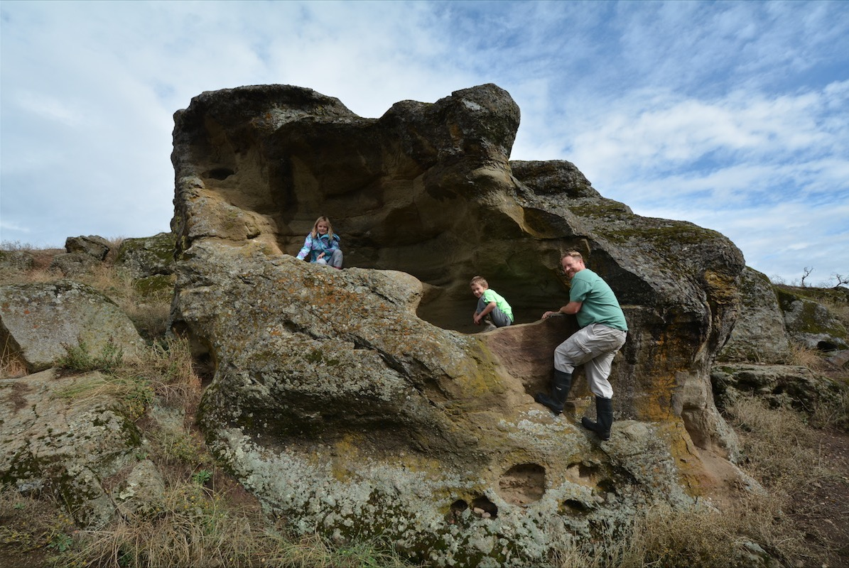 A family climbs a large rock outcropping on a family farm outside of Medford Oregon