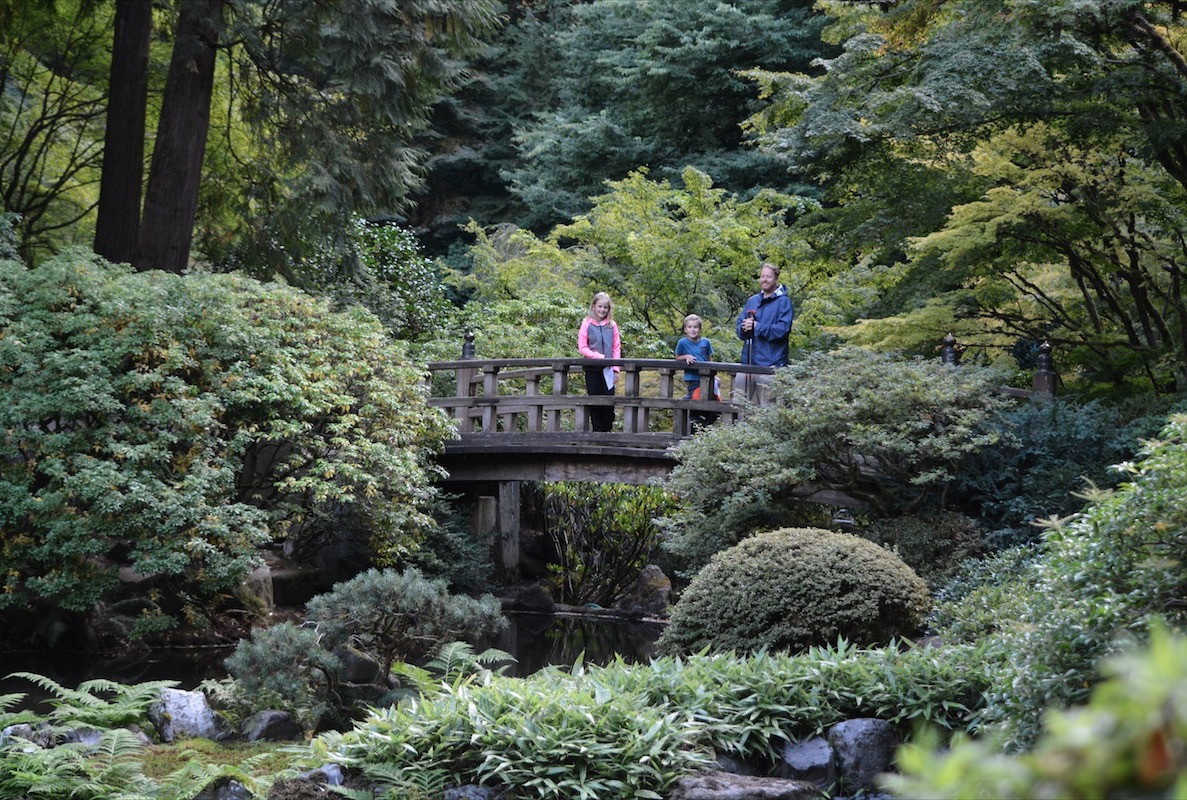 A family on a wooden bridge overlooking a pond in Portland public parks