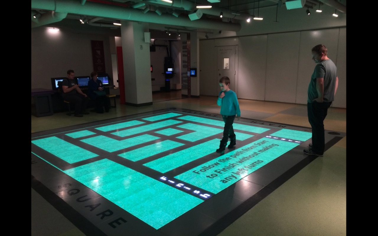 A young boy solves an electronic logic puzzle (maze) in Seattle's Children Museum