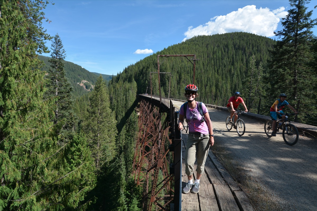 A woman stands on a high trestle bridge of the Route of the Hiawatha Mountain Bike Trail, and watches two more bikers ride by