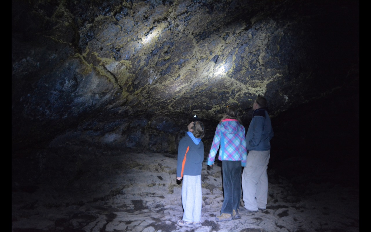 A family stands in the dark studying lava caves by the light of their headlamps in Lavabeds National Monument, California