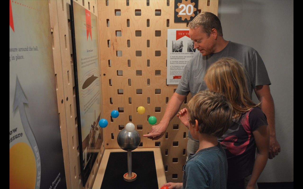 A father and his kids study an exhibit about air pressure and lift in a local kids musem