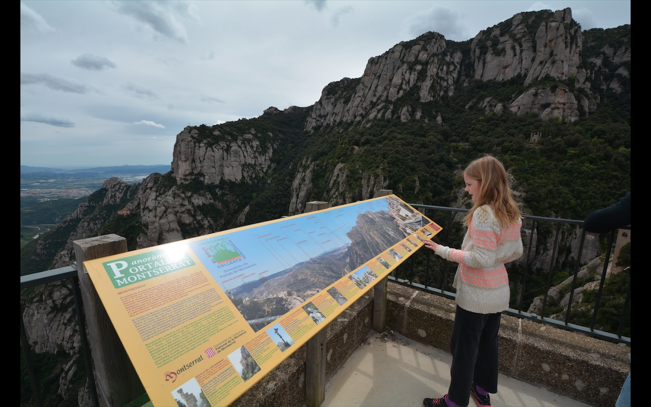 A girl studies a signboard on Montserrat, Spain
