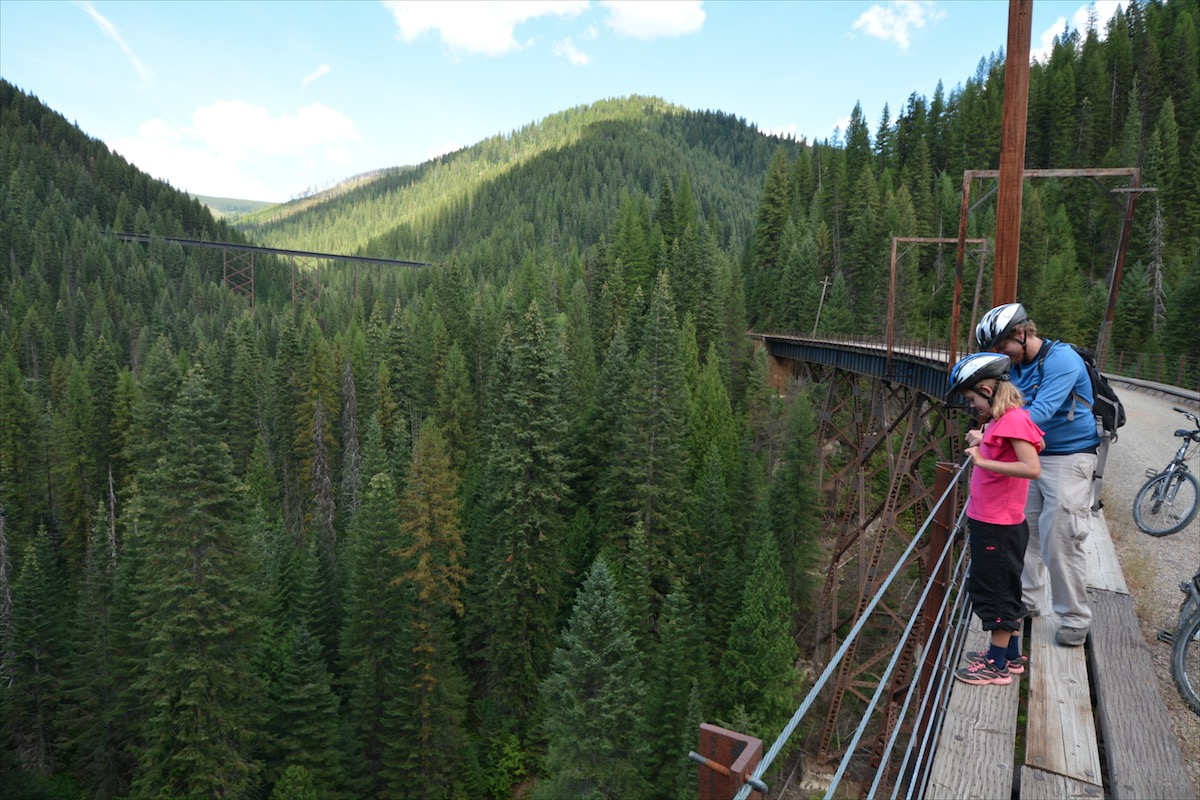 A father and daughter look down from high above the forest floor, atop a trestle bridge along the Route of the Hiawatha Mountain Bike Trail near Roland, Idaho