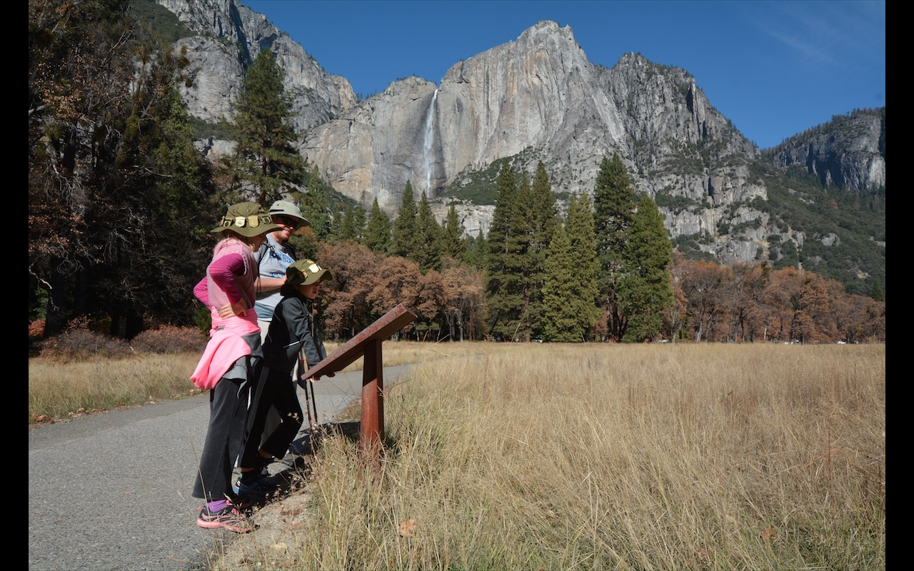 A family studies a signboard in Yosemite National Park