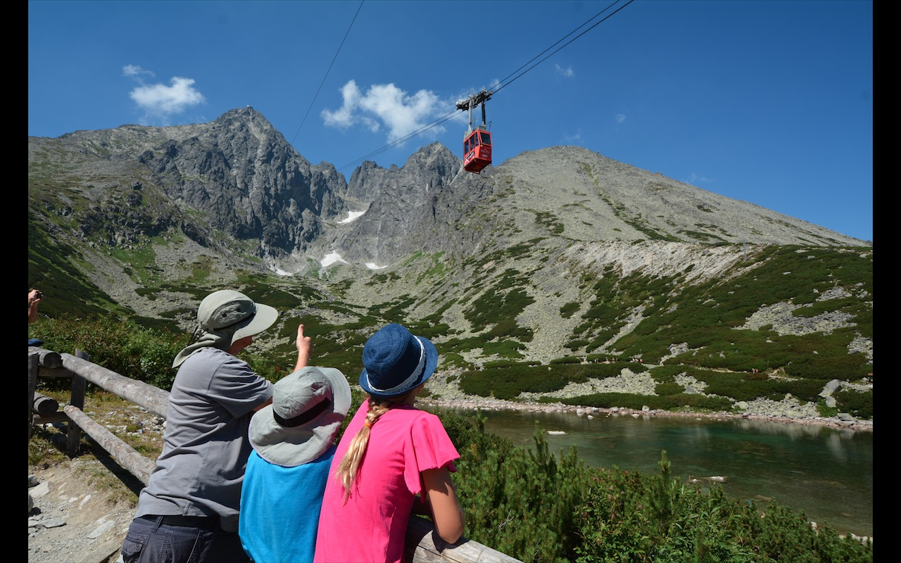 A family on Skalnate Plelso watches the gondola climb to Lomnicky Stit in Slovakia's Tatra Mountains