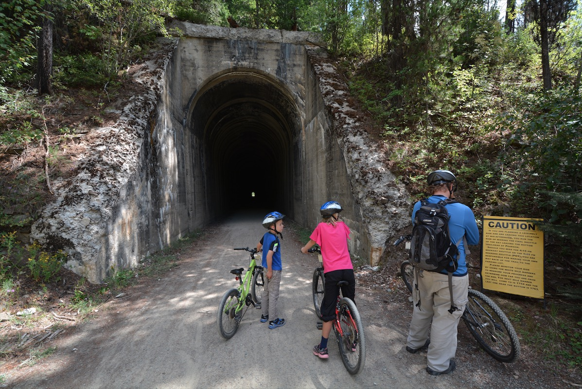 Father and children read the caution sign at the mouth of a tunnel along the Route of the Hiawatha Mountain Bike Trail near Roland, Idaho